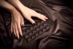 Female hands touching the dark chocolate bar Royalty Free Stock Photo