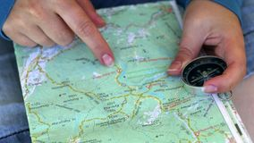 Female hands with travel map and compass. Female hands hold travel map and compass with moving needle, pointing and searching route, direction and destination stock video footage