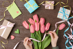 Female hands with tulips and gift box on wood Stock Photos