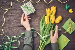 Female hands with tulips and gift box on wood Stock Image