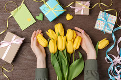 Female hands with tulips and gift box on wood Royalty Free Stock Photos