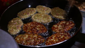 Female Hands Turning Meat Cutlets in a Frying Pan. stock footage