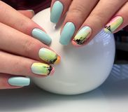 Female hands with a turquoise manicure and a painted ship. interesting and fashionable design stock photography