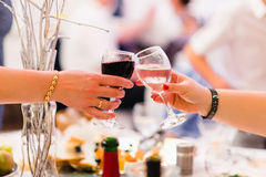 Female hands with two wine glasses clink Royalty Free Stock Photography