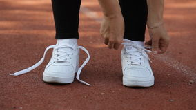 Female hands tying shoelace on running shoes before practice. Sport active lifestyle concept. Close-up stock video footage