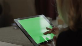 Female hands typing on green screen tablet pc sitting at table in cafe. Woman using green screen tablet computer. Mockup chroma key in tablet screen stock footage