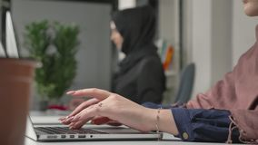 Female hands typing on the keyboard, close-up. Girl in black hijab in the background. Office, business, work, women. Concept. Arabs, Islam, hijab religion 60 stock video