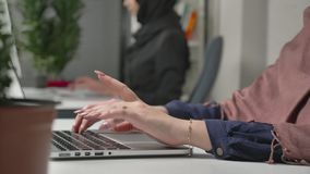 Female hands typing on the keyboard, close-up. Girl in black hijab in the background. Office, business, work, women. Concept. Arabs, Islam, hijab religion 60 stock footage