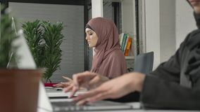 Female hands typing on the keyboard, close-up. Girl in pink hijab in the background. Office, business, work, women. Concept. Arabs, Islam, hijab religion 60 stock video