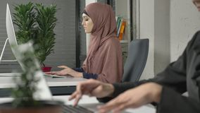 Female hands typing on the keyboard, close-up. Girl in pink hijab in the background. Office, business, work, women. Female hands typing on the keyboard, close-up stock footage