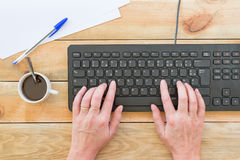 Female hands typing on the keyboard of a computer, on a vintage wood table. Female hands typing on the keyboard of a computer, on a vintage wooden table stock images