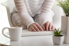 Female hands typing on a keyboard. Detail of female hands typing on a computer keyboard; woman drinking coffee and working on computer. Selective focus on the royalty free stock images