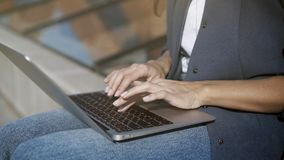 Female hands typing on a keyboard. In a small laptop outdoors stock photo