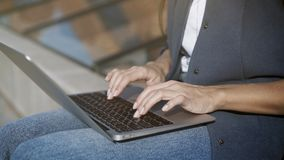 Female hands typing on a keyboard. In a small laptop outdoors in the summer royalty free stock photography