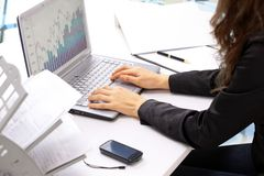 Female hands typing on the keyboard. And while holding the mouse. Analysis of the graphs of sales royalty free stock image