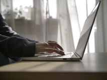 Female hands are typing on the keyboard of the laptop on the background of the window, close-up stock images