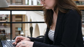 Female hands typing on the keyboard of a laptop in shopping mall.  Stock Photography