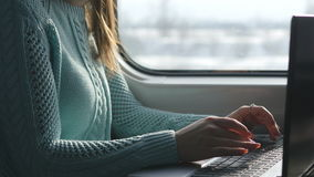 Female hands typing on keyboard of laptop in train. Woman chatting with friends during traveling on railway. Young girl stock video footage