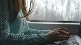 Female hands typing on keyboard of laptop in train. Woman chatting with friends during traveling on railway. Young girl. Using notebook. Arm print a message stock photography