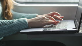 Female hands typing on keyboard of laptop in train. Woman chatting with friends during traveling on railway. Young girl. Using notebook. Arm print a message stock video footage