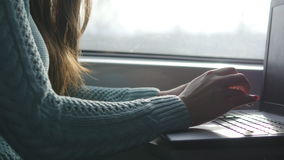 Female hands typing on keyboard of laptop in train. Woman chatting with friends during travelling on railway. Young girl. Using notebook. Arm print a message royalty free stock images