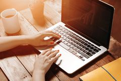 Female hands typing on the keyboard. Of a laptop on vintage wooden table. Mock-up with laptop royalty free stock images