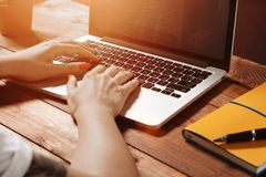 Female hands typing on the keyboard. Of a laptop on vintage wooden table. Mock-up with laptop stock image