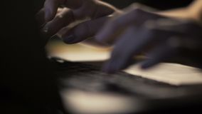 Female hands typing on keyboard on modern laptop computer in dark interior. Female hands typing on notebook keyboard in dark interior. Close up woman hands using stock footage