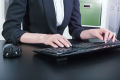 Female hands typing on the keyboard. In the office stock photos
