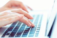 Female hands typing on the keyboard. Female hands or woman office worker typing on the keyboard stock image