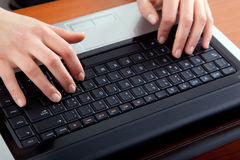 Female hands typing on a laptop Stock Photography