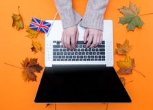 Female hands typing at laptop computer near Great Britain flag Stock Photos