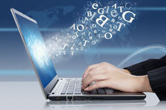 Online business. Female hands typing on the laptop with flying letters Royalty Free Stock Images