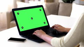 Female hands typing on laptop with green screen. Technology concept - female hands typing on laptop with green screen and smartphone on table stock video footage