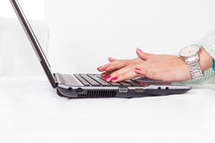 Female hands typing on laptop keyboard with red nail polish Stock Images