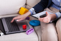 Female hands typing on laptop and kids toys Royalty Free Stock Photos