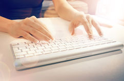 Female hands typing on a white computer keyboard. Photo of female hands typing on a white computer keyboard royalty free stock photo