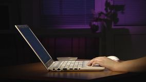 Female hands typing on a white laptop. Evening. Evening. On the table is a laptop. The woman is typing, drinking tea or coffee. Close-up stock footage