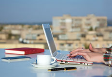 Female Hands Typing on White Laptop Keyboard. At Roof Top Cafe Terrace with Urban Landscape on Background Royalty Free Stock Photo