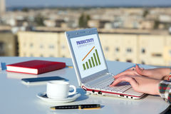 Female Hands Typing on White Laptop Keyboard at Roof Top Cafe. Terrace with Urban Landscape on Background and Colorful Chart on Screen Royalty Free Stock Images