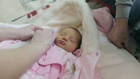 Female hands undress newborn baby girl. stock footage