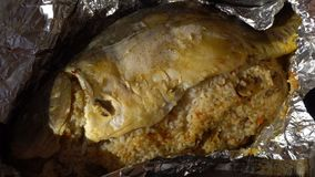 Female hands unfolding of baked fish in foil.  stock footage
