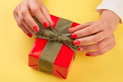Female hands unpacking red gift box. Young woman manicured hands opening red box with present  on yellow background. Holiday present concept Royalty Free Stock Photo