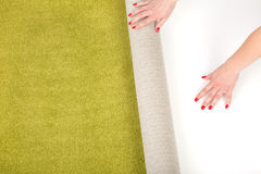 Female hands unrolling a carpet Royalty Free Stock Photos