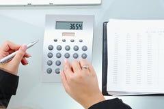 Female hands using calculator stock photos