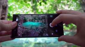 Female hands using cell phone for taking photo of Sra Morakot Blue Pool at Krabi Province in Thailand. Famous Natural. Attraction in Krabi shot with Sony a6300 stock footage