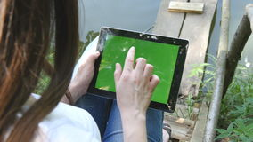 Female hands using digital tablet pc with green screen sitting on a wooden jetty by the lake. stock video
