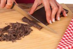 Chopping dark chocolate for cake Royalty Free Stock Photos