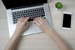 Female hands using laptop with empty black screen on wooden desktop royalty free stock photo