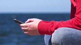 Female hands using mobile smart phone at ocean pier. Young woman hands using mobile smart phone at the edge of wooden ocean pier, close up, sending sms text stock video